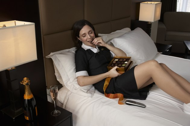 Chambermaid relaxing on bed, eating chocolates