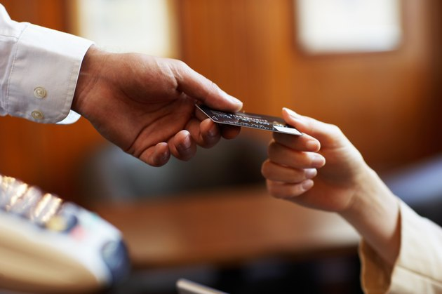 Young woman handing waiter credit card, close-up