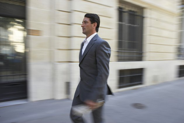 France, Paris, businessman in street (blurred motion)