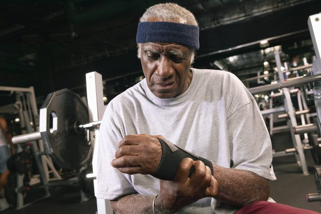Senior man applying wrist strap in gym, close-up