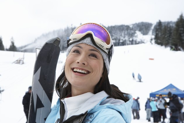 Woman with skis at base of mountain near ski lift, smiling, looking up