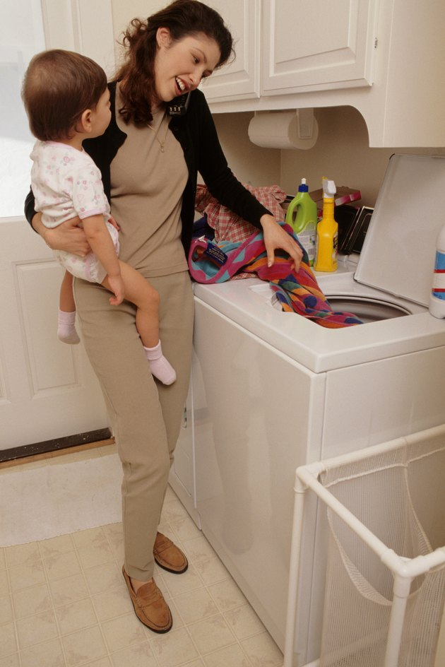 Mother holding baby girl (21-24 months), doing laundry in wash room