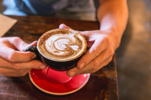 Man holding cappuccino with froth art