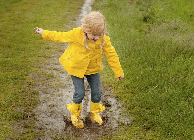 Girl Jumping in Mud Puddle