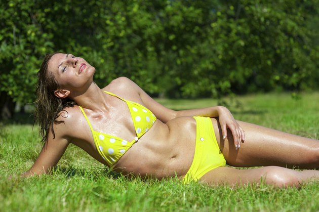 The young girl in a bathing suit sunbathes