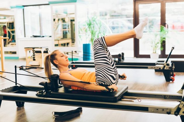 Woman doing  workout exercises on pilates reformer at gym