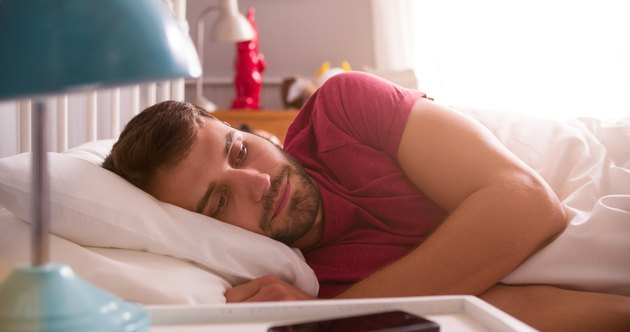 Man Lying Awake In Bed Looking Worried