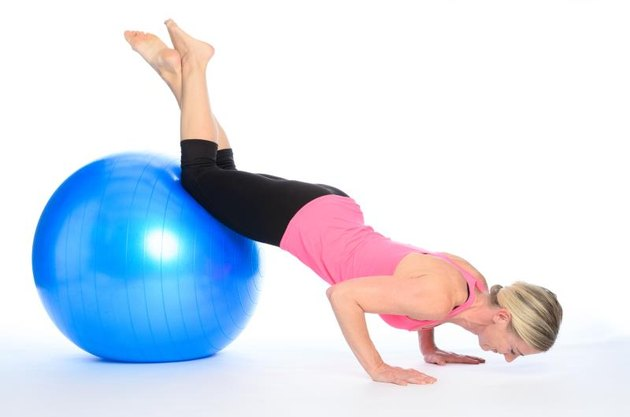 Athletic woman doing pilates exercises balancing with her knees on the ball doing press ups while controlling and strengthening her muscles, over white