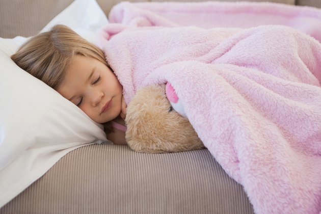 Close-up of a girl sleeping on sofa with stuffed toy