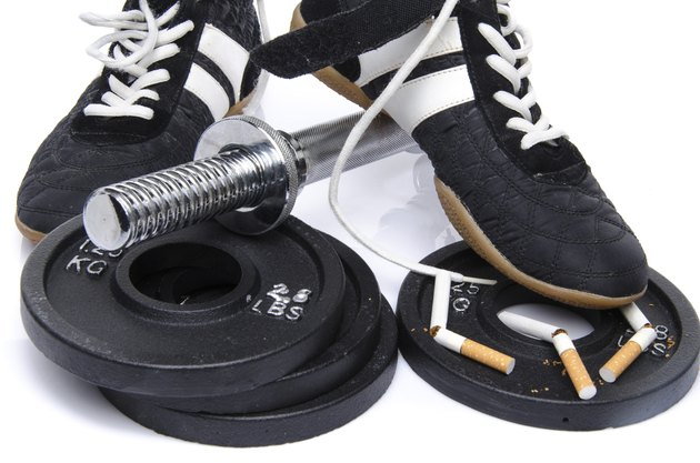 Dumbells, fitness shoes with broken cigarettes