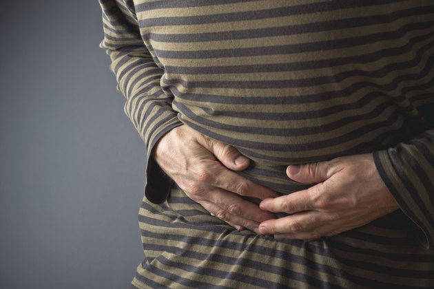 Abdominal Pain. Man holds his stomach and has hurt