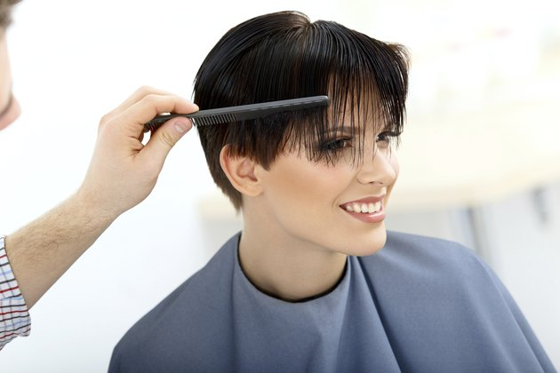 Brunette with Short Hair in Salon. Hairdresser doing Hairstyle