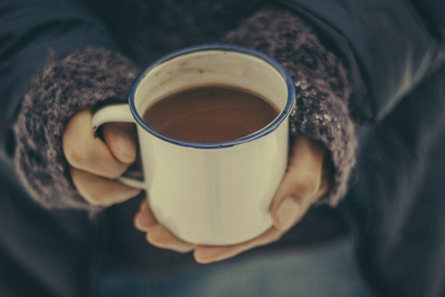 Hands holding a cup of hot chocolate in winter