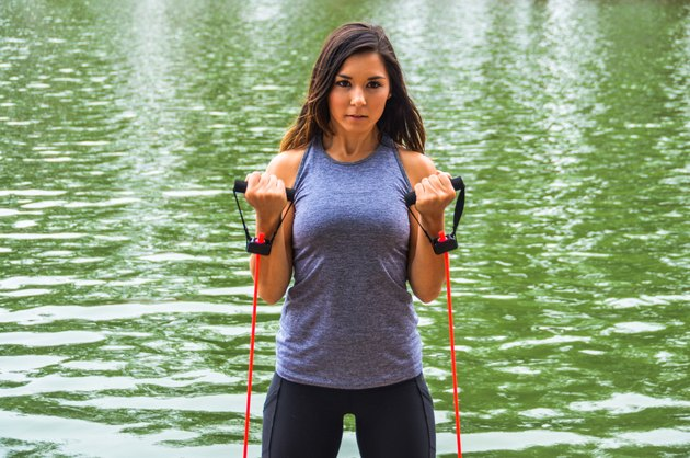 Athletic skinny woman using resistance bands