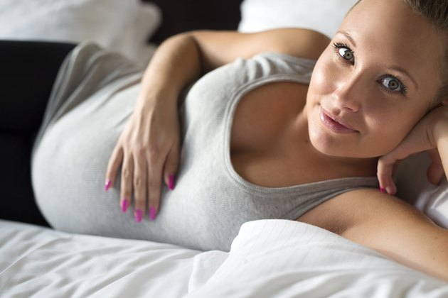 Smiling pregnant woman on bed with her hand at belly