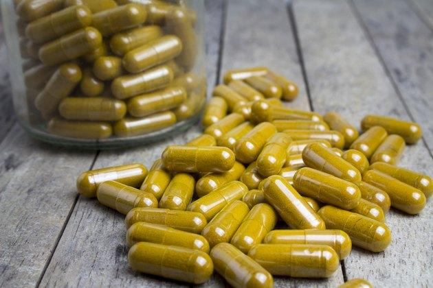 herbal capsules drug on wood board