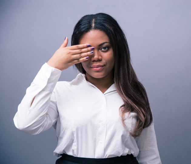 African businesswoman covering one eye with hand