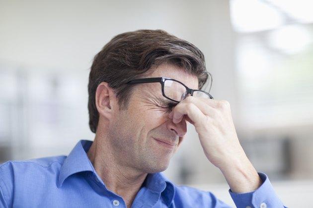 Mature man wincing with a headache