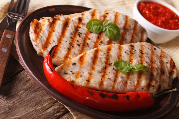 Grilled chicken breast and chili pepper on a plate horizontal