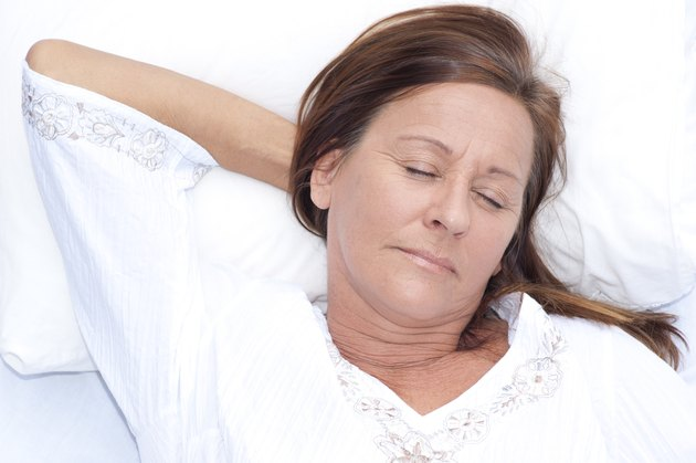 Relaxed mature woman asleep in bed