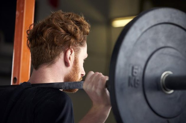 Rear View Of Young Man In Gym Lifting Weights On Barbell