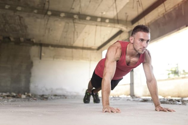 Muscular, athletic built, young man doing pushups in an abandoned ruin building