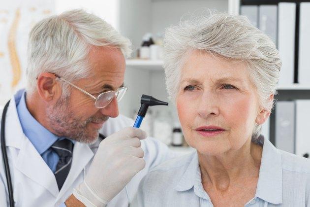 Doctor examining senior patient's ear