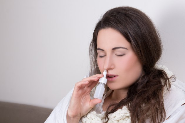 woman using nasal spray in her living room