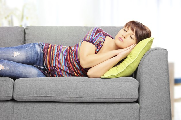 Young female sleeping on sofa at home