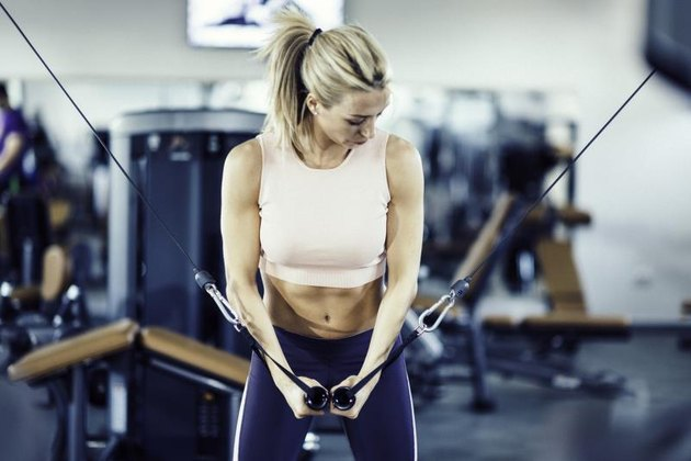 Attractive girl working out on cable crossover exercising machine