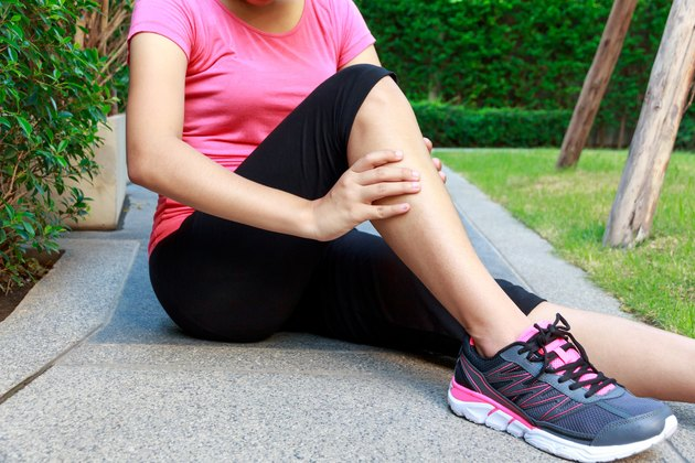 Asian sporty woman leg pain or calf muscle while jogging