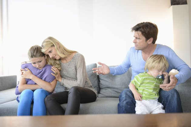Mother consoling daughter as father sits with son on sofa