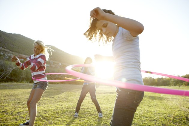 Teenage girls hula-hooping together