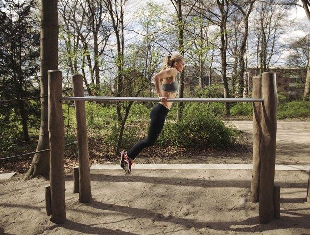 Fitness female doing parallel bar dips