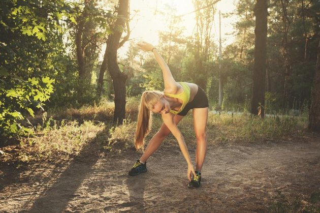 Young sportswoman stretching. Beautiful sporty girl does sport exercises in forest at colorful sunset in summer evening. Fitness model workout. Beautiful fitness athlete woman