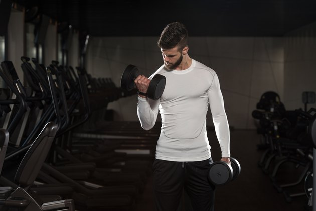 Handsome Man Exercising Biceps With Dumbbells