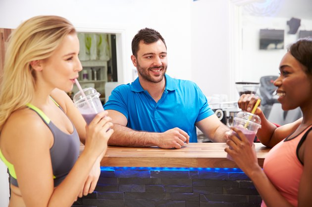 People drinking protein shakes at the fitness bar in gym
