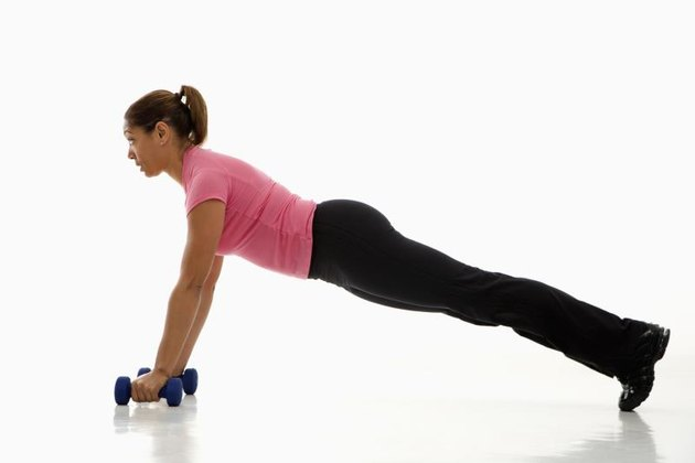 Side view of mid adult multiethnic woman wearing pink exercise shirt doing pushups while holding dumbbells.