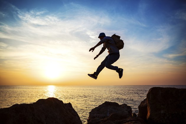 brave man jumping at sunset
