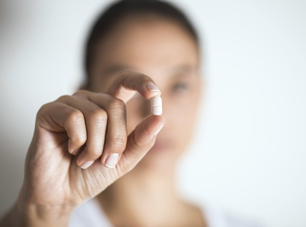 Woman Holding And Showing Medication Capsule