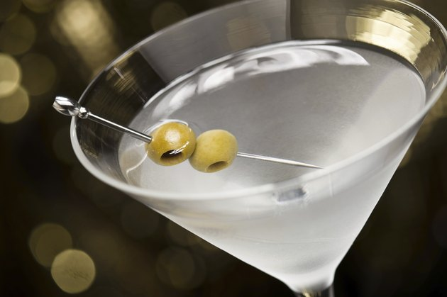Vodka Martini with olive garnish in front of a gold