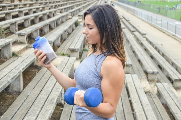 Woman drinking a protein shake and lifting weights
