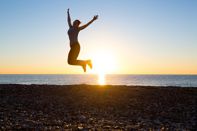 Silhouette Happy Female jumping high with arms raised beach sunrise