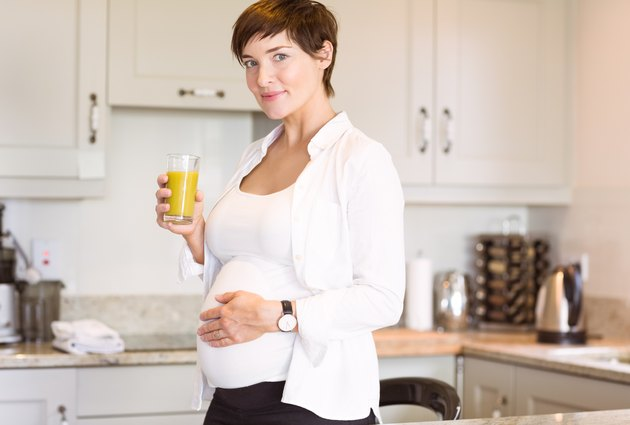 Pregnant woman having a glass of orange juice