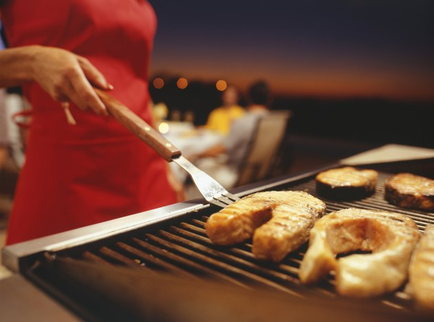 Woman barbecuing, close-up, mid section