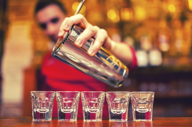 barman pouring cocktail drinks into shot glasses