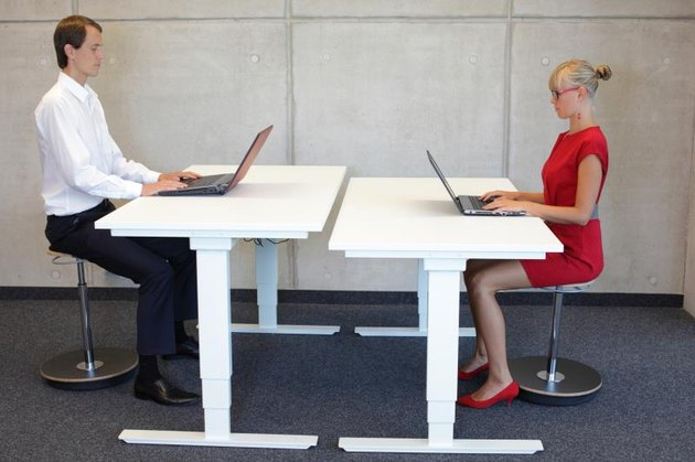 business man and woman coworking in correct sitting posture on pneumatic leaning seats with laptops at electric height adjustable desks in office