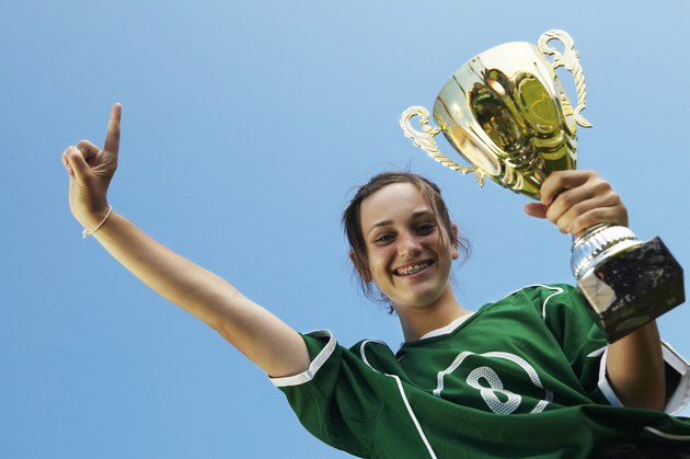 Female (11-13) footballer with trophy, other hand raised, smiling