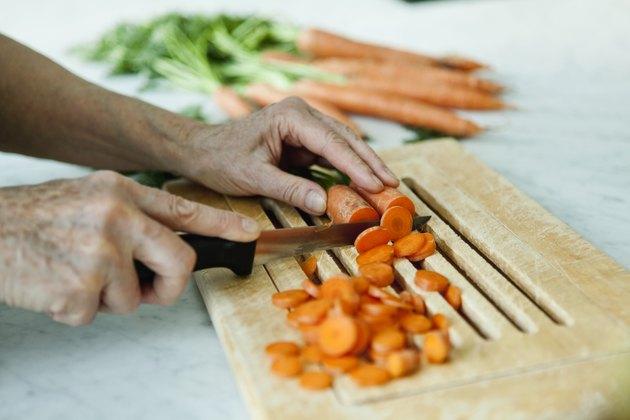Germany, Berlin, Senior man cutting carrots