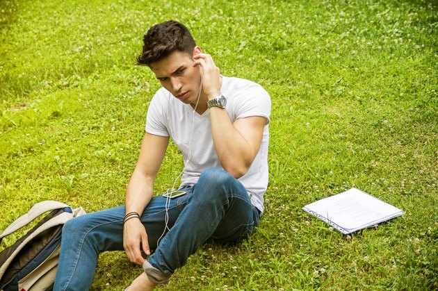 Young Man Listening to Music in Park